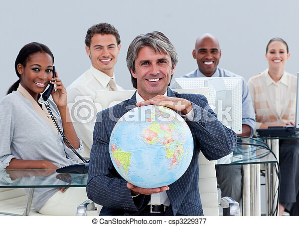 Fortunate business team at work showing a terrestrial globe  - csp3229377
