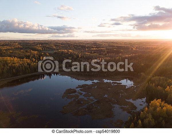 Una foto aérea de un atardecer sobre el bosque en el día de otoño - csp54019800
