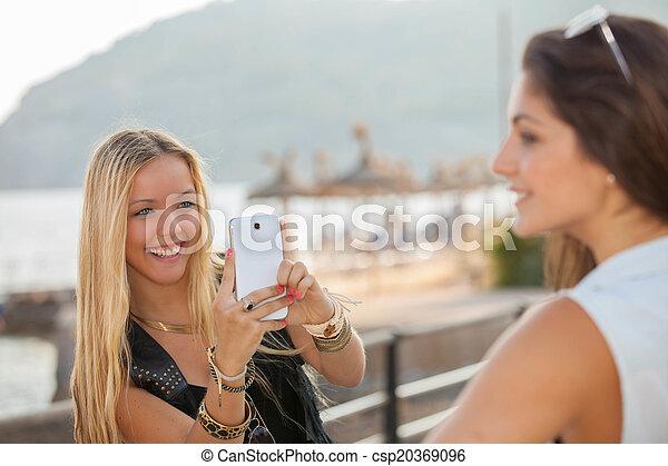 Adolescentes tomando fotos con un teléfono genérico inteligente - csp20369096