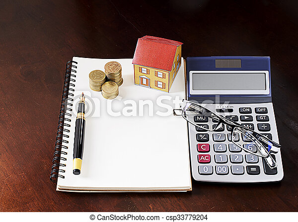 Fountain pen with coins stack and paper house and calculator and glasses on wooden desk table - csp33779204