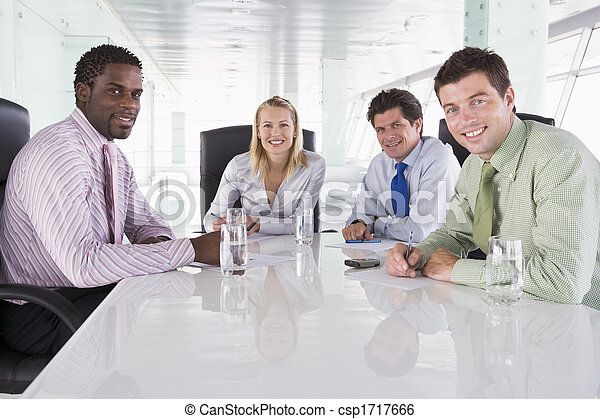 Four businesspeople in a boardroom smiling - csp1717666