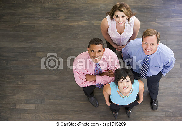 Four businesspeople standing indoors smiling - csp1715209