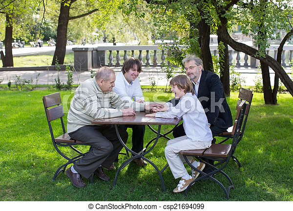 Four generations of men sitting at a wooden table in a park, laughing and talking - csp21694099