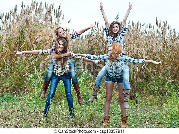 Four happy teen girls friends having fun outdoors - csp13357911
