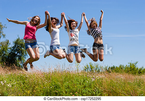 Four happy teen girls friends jumping high against blue sky - csp17252295