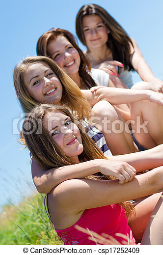 Four happy teen girls sitting together against blue sky - csp17252409
