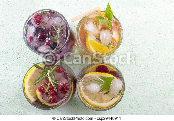 Four non alcoholic fruit cocktails arranged on the green table top view - csp29446911