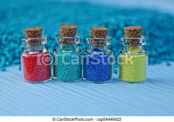 four small glass bottles with colored sand - csp54446422
