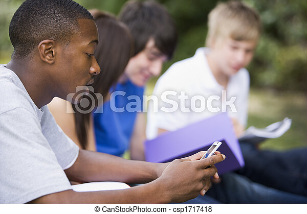 Four students outdoors studying with one checking cellular phone (depth of field) - csp1717418