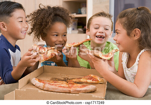Four young children indoors eating pizza smiling - csp1717249