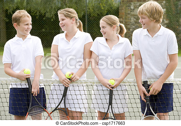 Four young friends with rackets on tennis court smiling - csp1717663