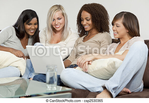 Four Young Women Friends Having Fun Using A Laptop Computer - csp2530365