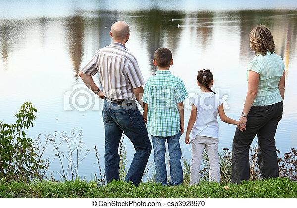Familie mit zwei Kindern im frühen Herbst Park nahe Teich. Sie schauen auf Wasser. - csp3928970