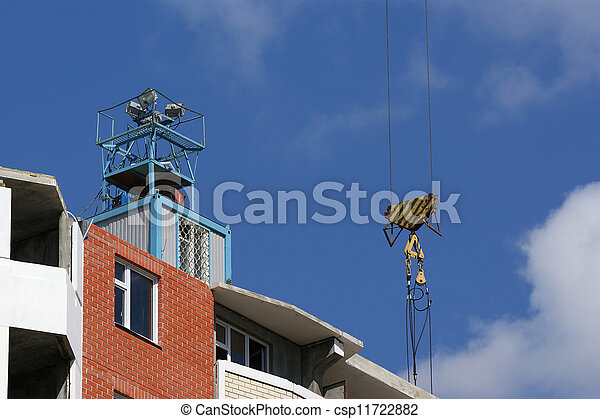 Fragment of a residential apartment building under construction on a background of blue sky - csp11722882
