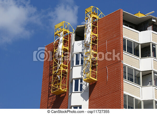 Fragment of a residential apartment building under construction on a background of blue sky - csp11727355