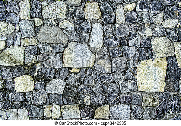 Fragment of old brick wall with river stones texture white grey brown black green blue lime yellow orange maroon violet pink turquoise colored background, different type of stones mosaic surface - csp43442335