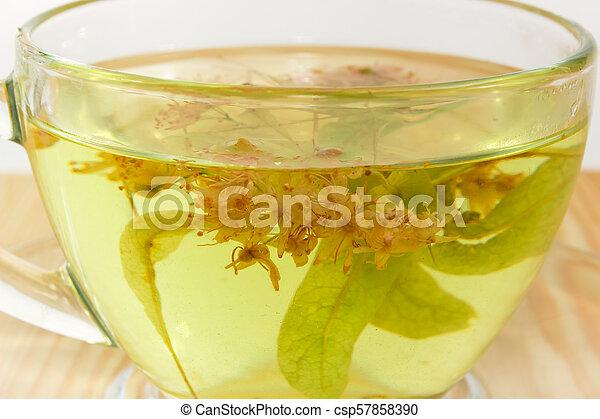 Fragment of transparent glass cup with linden flower tea closeup - csp57858390