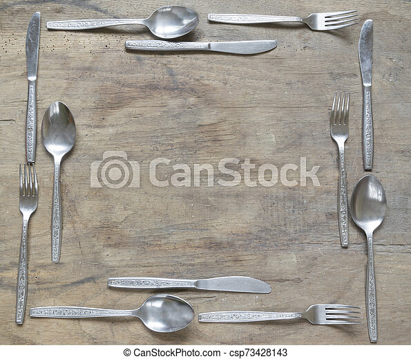 Frame from silver spoons, knives and forks on old wooden background - csp73428143