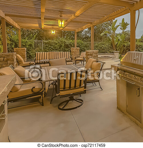 frame Outdoor kitchen and dining area under a pergola at the spacious patio  of a home