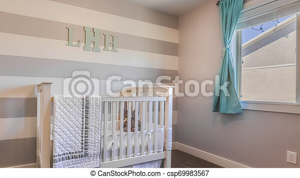 frame Panorama Interior of a nursery with white crib and monogram letters on the striped wall - csp69983567