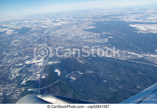 FRANKFURT, GERMANY - JAN 20th, 2017: View through aircraft window onto jet wing, wingview over snow covered city of Frankfurt am Main, airport FRAPORT in the background - csp52841587