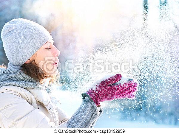 Schöne Winterfrau, die draußen Schnee bläst - csp13132959