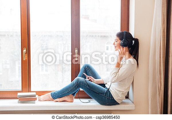Frau Fensterbank Sitzen Musik Horen Lacheln Frau Fensterbank