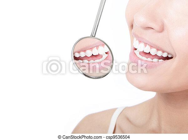 Gesunde Frauenzähne und Zahnarzt-Mundspiegel - csp9536504