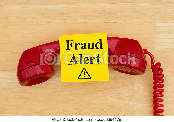 Fraud alert on sticky note with a retro red phone on textured wood desk - csp68694479