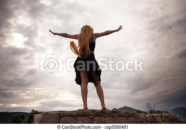 Freedom concept - woman on mountain peak - csp5580481