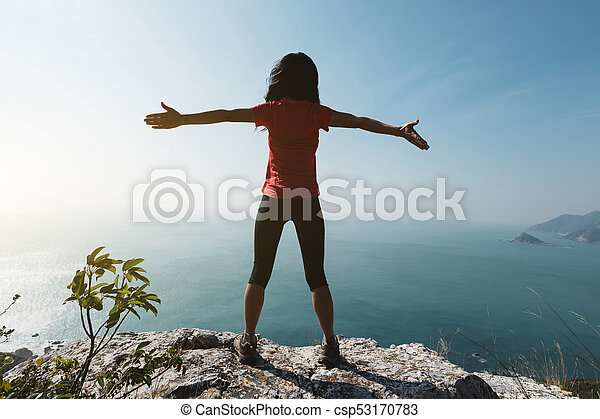 freedom female standing with outstretched arms on sunrise windy coast