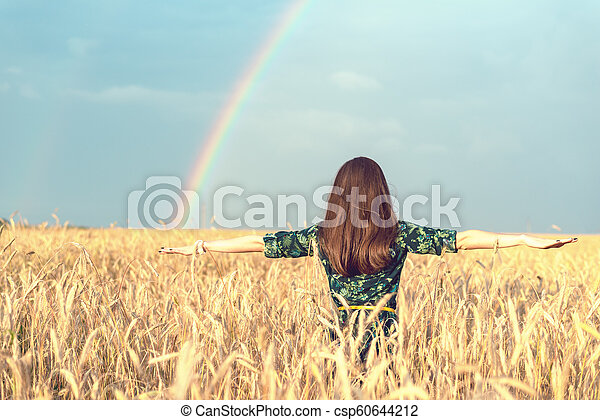 Freedom. Happy smiling woman with open hands in wheat field with Golden spikelets looking up at the sky on rainbow background - csp60644212