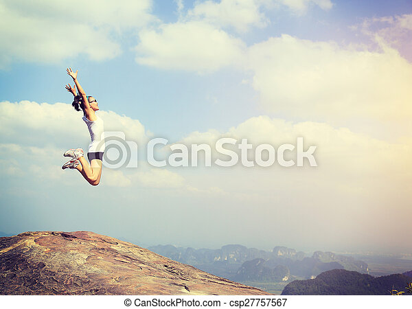freedom young asian woman jumping on mountain peak rock - csp27757567