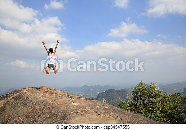 freedom young asian woman jumping on mountain peak rock - csp34547555