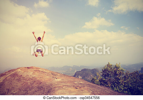 freedom young asian woman jumping on mountain peak rock - csp34547556