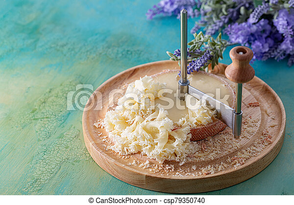 French cheese Monk Head sliced with clove petals on a wooden round surface. Bouquet of lavender. - csp79350740