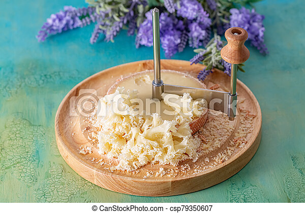 French cheese Monk Head sliced with clove petals on a wooden round surface. Bouquet of lavender. - csp79350607