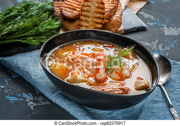 French fish soup Bouillabaisse with seafood, salmon fillet, shrimp, rich flavor, delicious dinner. Close up - csp62376917