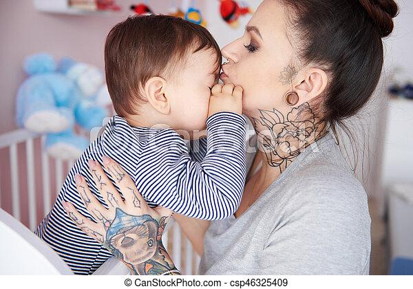 Madre besando a su hijo dormilón en la frente - csp46325409