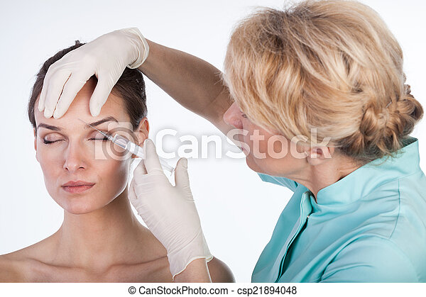 Doctor inyectando botox en la frente - csp21894048
