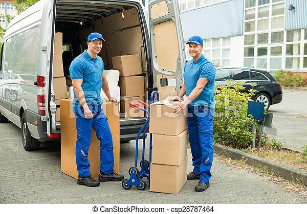 Trabajador con cajas de cartón delante del camión - csp28787464