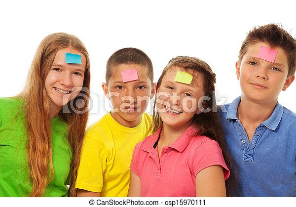 Cuatro niños con pegatinas en la frente - csp15970111
