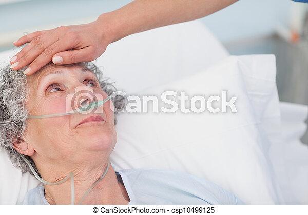 La enfermera toca la frente de un paciente - csp10499125