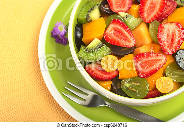 Fresh and healthy fruit salad with strawberry, kiwi, grape, mango and physalis in a bowl with fork and small blue flowers photographed from above (Selective Focus, Focus from the front to the middle o - csp6248716