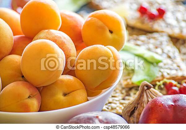 Fresh apricots in a white dish and other fruits on the kitchen table. Healthy lifestyle - csp48579066
