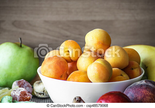 Fresh apricots in a white dish and other fruits on the kitchen table. Healthy lifestyle - csp48579068
