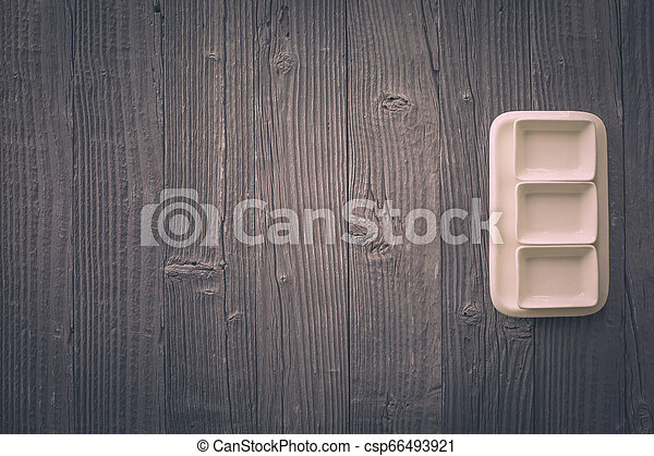 Fresh asparagus served on white plate with mortar on rustic wooden table background, top view. - csp66493921
