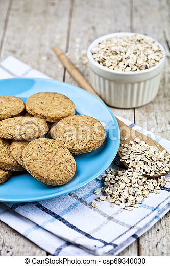 Fresh baked oat cookies on blue ceramic plate on linen napkin and oak flakes on rustic wooden table. - csp69340030