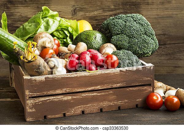 Fresh bio vegetables in wooden crate with radish, salad, mushrooms, broccoli, tomatoes - csp33363530
