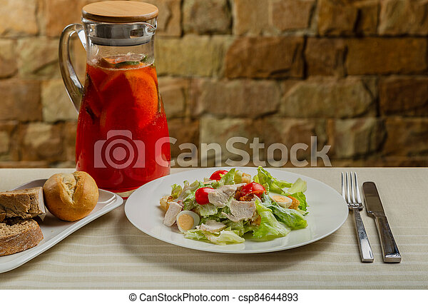 Fresh caesar salad in a white plate on the table. - csp84644893
